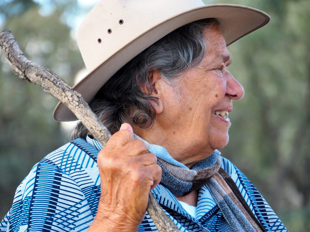 Aboriginal woman wearing a hat and holding  a stick